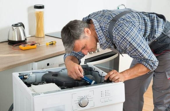 Appliance repairman in Plano fixing a whirlpool washer. The washing machine is pulled out of the counter and he is repairing the appliance with his tool.